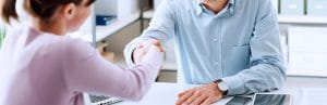 Two people waving hand in an office, healthy client relationships